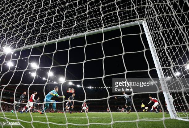 Aaron Ramsey of Arsenal scores past Igor Akinfeev of CSKA Moskva during the UEFA Europa League quarter final leg one match between Arsenal FC and...