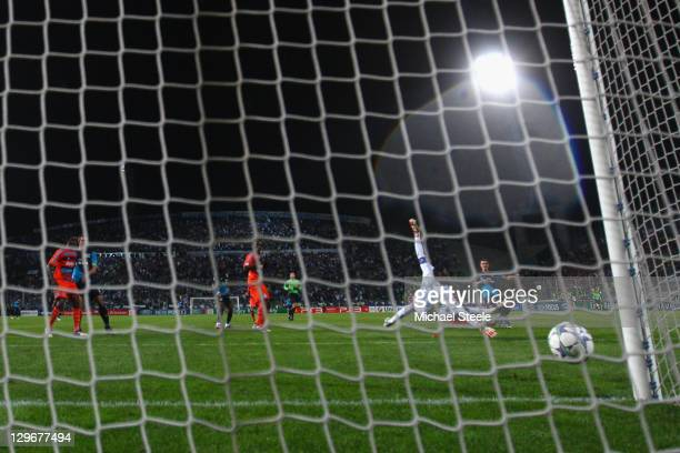 Aaron Ramsey of Arsenal scores the winning goal in injury time past the dive of goalkeeper Steve Mandanda during the UEFA Champions League Group F...