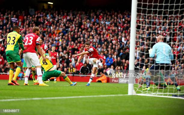 Aaron Ramsey of Arsenal shoots past goalkeeper John Ruddy of Norwich City to score their third goal during the Barclays Premier League match between...