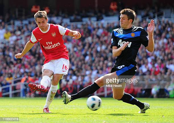 Aaron Ramsey of Arsenal shoots past Michael Carrick of MAnchester United to score their first goal during the Barclays Premier League match between...