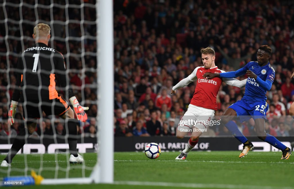 Aaron Ramsey of Arsenal shoots past Wilfred Ndidi of Leicester City to score his team's third goal during the Premier League match between Arsenal and Leicester City at the Emirates Stadium on August 11, 2017 in London, England.