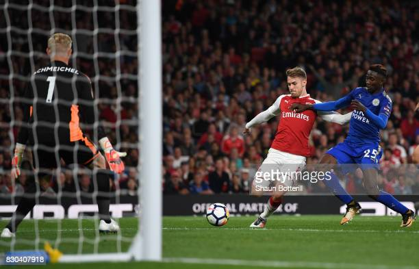 Aaron Ramsey of Arsenal shoots past Wilfred Ndidi of Leicester City to score his team's third goal during the Premier League match between Arsenal...