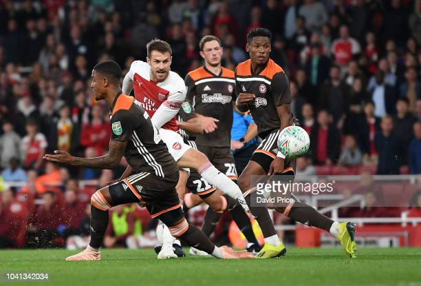Aaron Ramsey of Arsenal shoots under pressure from Julian Jeanvier of Brentford during the Carabao Cup Third Round match between Arsenal and...