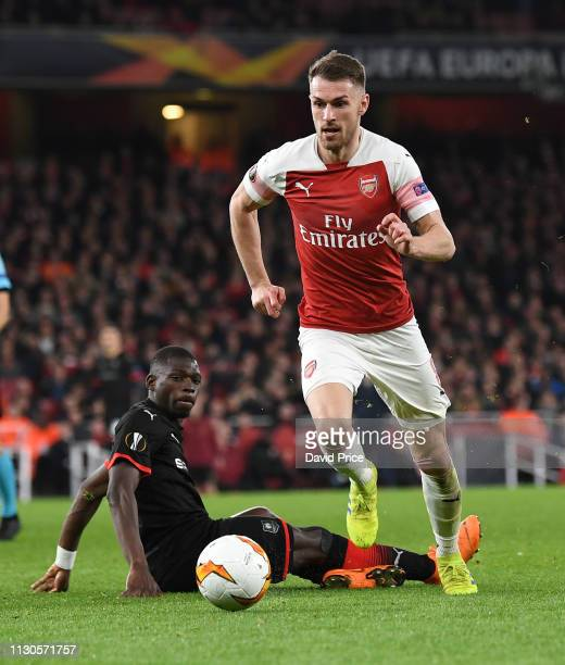 Aaron Ramsey of Arsenal skips past Hamari Traore of Rennias during the UEFA Europa League Round of 16 Second Leg match between Arsenal and Stade...