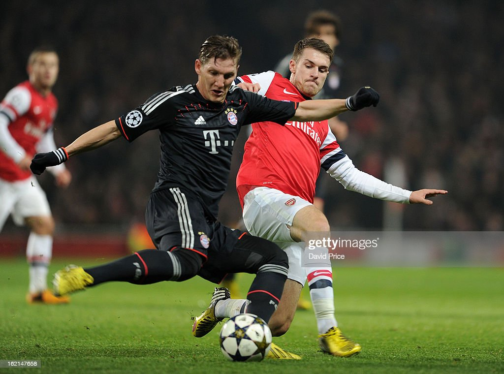 Aaron Ramsey of Arsenal tackles Bastian Schweinsteiger of Bayern during the UEFA Champions League Round of 16 first leg match between Arsenal FC and Bayern Muenchen at Emirates Stadium on February 19, 2013 in London, England.