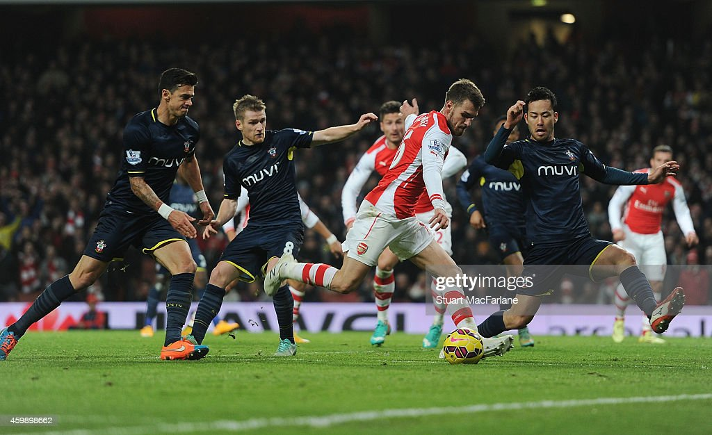 Aaron Ramsey of Arsenal takes on (L) Jose Fonte (2ndL) Steve Davis and (R) Maya Yoshida of Southampton during the Barclays Premier League match between Arsenal and Southampton at Emirates Stadium on December 3, 2014 in London, England.