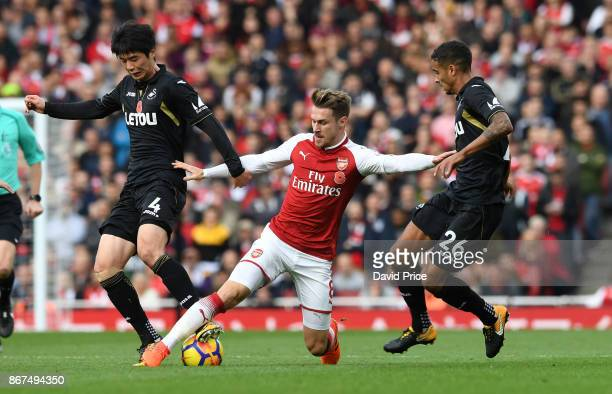 Aaron Ramsey of Arsenal takes on Ki SungYeung and Kyle Naughton of Swansea during the Premier League match between Arsenal and Swansea City at...
