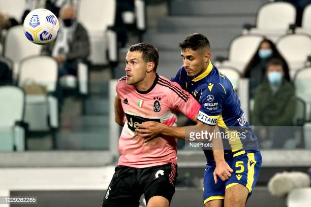 Aaron Ramsey of Juventus competes for the ball with Marco Faraoni of Hellas Verona FC during the Serie A match between Juventus and Hellas Verona FC...
