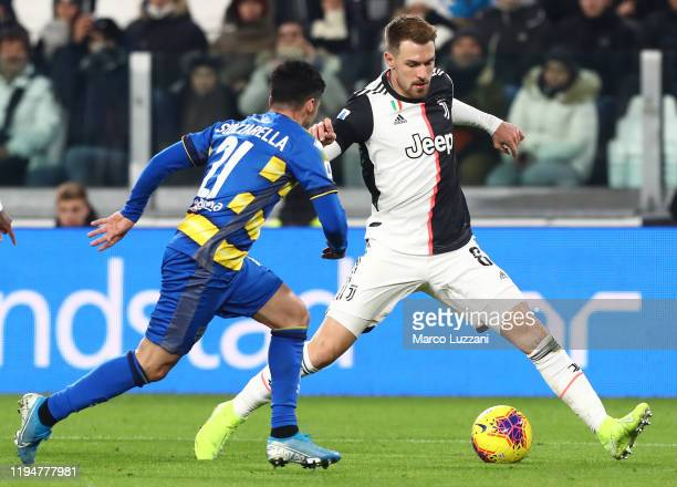 Aaron Ramsey of Juventus competes for the ball with Matteo Scozzarella of Parma Calcio during the Serie A match between Juventus and Parma Calcio at...