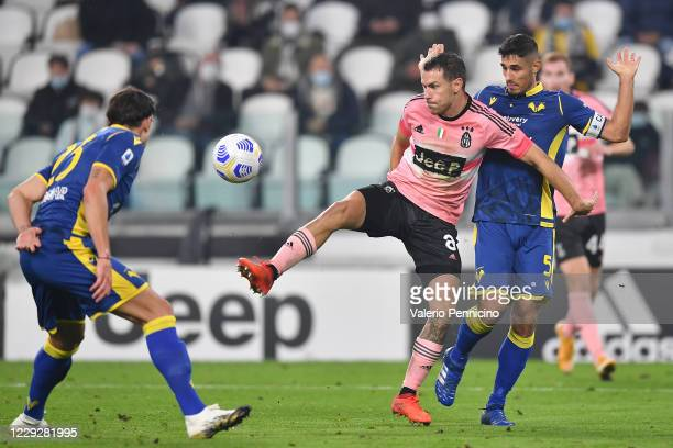 Aaron Ramsey of Juventus competes with Davide Faraoni of Hellas Verona FC during the Serie A match between Juventus and Hellas Verona FC at Allianz...
