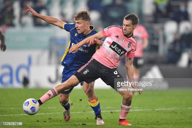 Aaron Ramsey of Juventus competes with Matteo Lovato of Hellas Verona FC during the Serie A match between Juventus and Hellas Verona FC at Allianz...