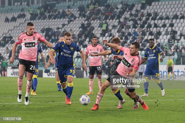 Aaron Ramsey of Juventus goes down in the penalty area under pressure from Matteo Lovato of Hellas Verona the referee Fabrizio Pasqua waved away the...