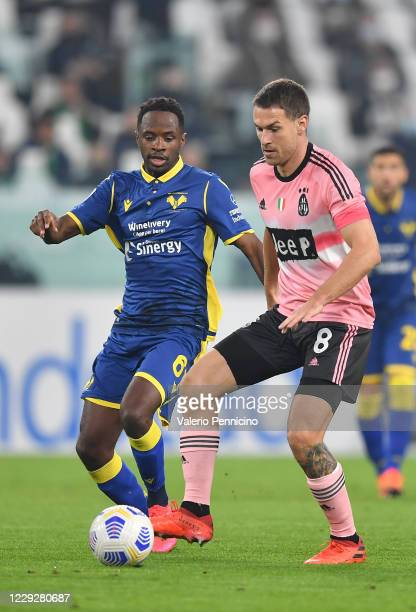 Aaron Ramsey of Juventus is challengede by Adrien Tameze of Hellas Verona FC during the Serie A match between Juventus and Hellas Verona FC at...
