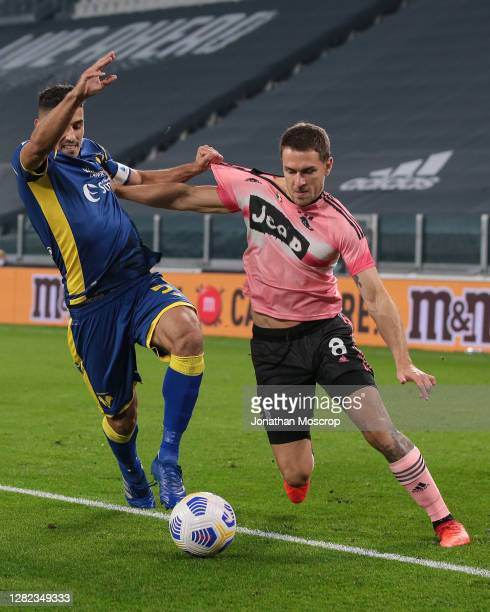 Aaron Ramsey of Juventus tussles with Davide Faraoni of Hellas Verona during the Serie A match between Juventus and Hellas Verona FC at Allianz...