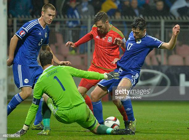 Aaron Ramsey of Wales in action against Mario Vrancic and goalkeeper Asmir Begovic of Bosnia during the Euro 2016 qualifying football match between...