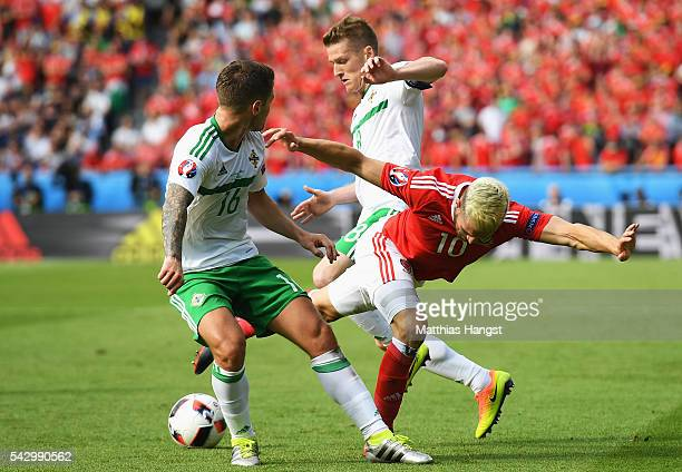 Aaron Ramsey of Wales is challenged by Oliver Norwood and Steven Davis of Northern Ireland during the UEFA EURO 2016 round of 16 match between Wales...