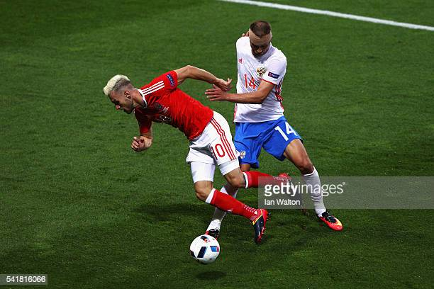 Aaron Ramsey of Wales is tackled by Vasili Berezutski of Russia during the UEFA EURO 2016 Group B match between Russia and Wales at Stadium Municipal...