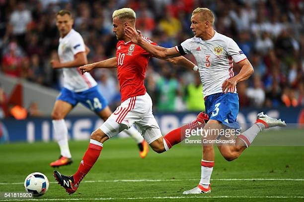 Aaron Ramsey of Wales runs past Igor Smolnikov of Russia to score his team's first goal during the UEFA EURO 2016 Group B match between Russia and...