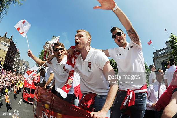 Aaron Ramsey Per Mertesacker and Olvier Giroud cheer at the Arsenal Victory Parade after winning the FA Cup Final on May 18 2014 in London England