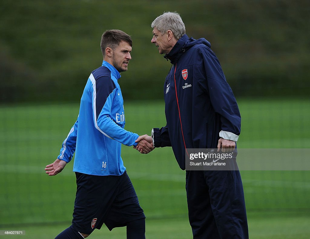 ST. ALBANS, ENGLAND - Aaron Ramsey shakes hands with Arsenal manager Arsene Wenger before a training session at London Colney on April 11, 2014 in St Albans, England.