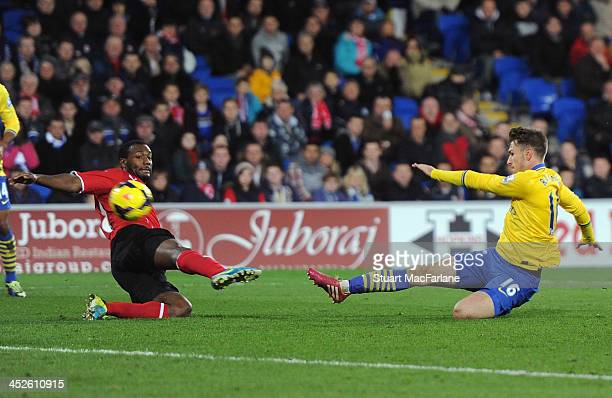 Aaron Ramsey shoots past Cardiff's Gary Medel to score the 3rd Arsenal goal during the match at Cardiff City Stadium on November 30 2013 in Cardiff...