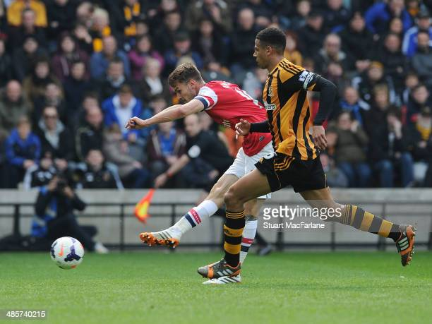 Aaron Ramsey shoots past Hull defender Curtis Davies to socre the 1st Arsenal goal during the Barclays Premier League match between Hull City and...
