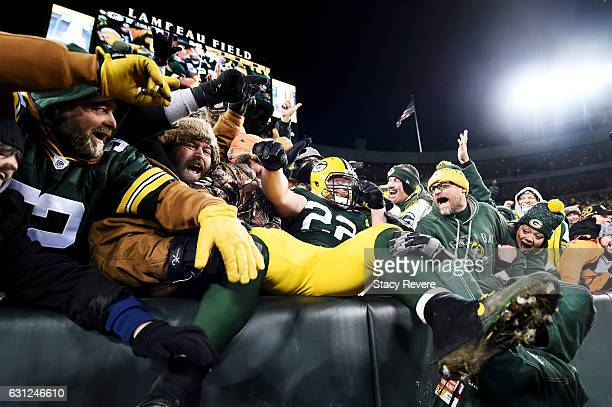 Aaron Ripkowski of the Green Bay Packers celebrates with fans after scoring a touchdown in the fourth quarter during the NFC Wild Card game against...