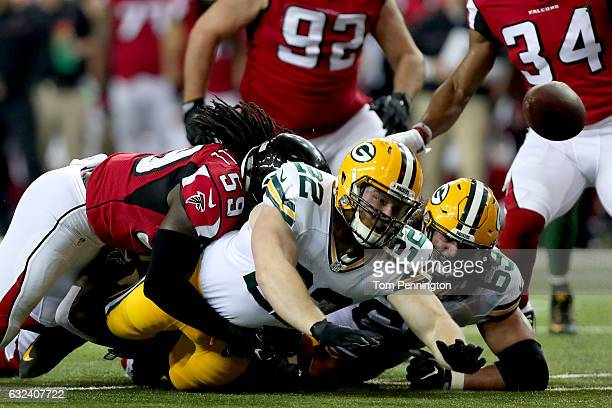 Aaron Ripkowski of the Green Bay Packers fumbles as he is tackled by De'Vondre Campbell of the Atlanta Falcons in the second quarter in the NFC...