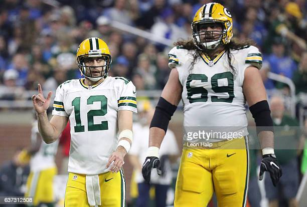 Aaron Rodgers and David Bakhtiari of the Green Bay Packers walk to the line during the second quarter of the game against the Detroit Lions at Ford...