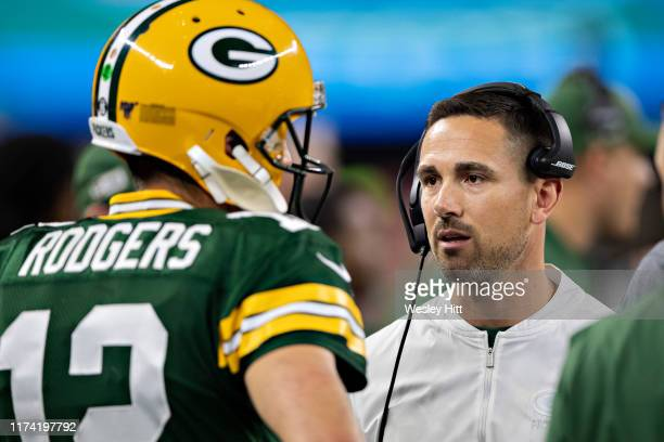 Aaron Rodgers and head coach Matt LaFleur of the Green Bay Packers talk on the sidelines during a game against the Dallas Cowboys at ATT Stadium on...