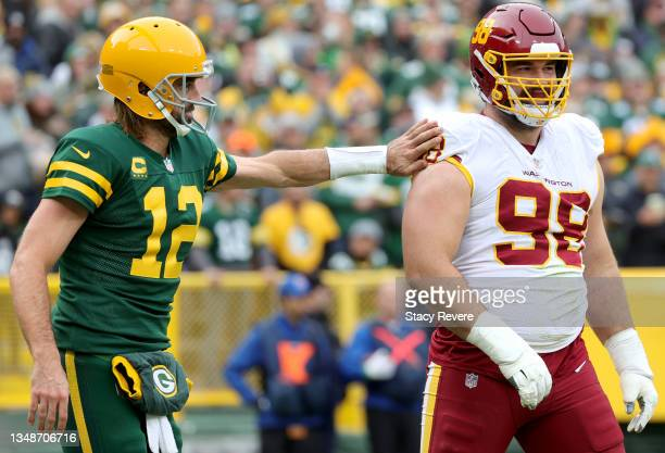 Aaron Rodgers of the Green Bay Packers and Matthew Ioannidis of the Washington Football Team meet in the third quarter in the game at Lambeau Field...