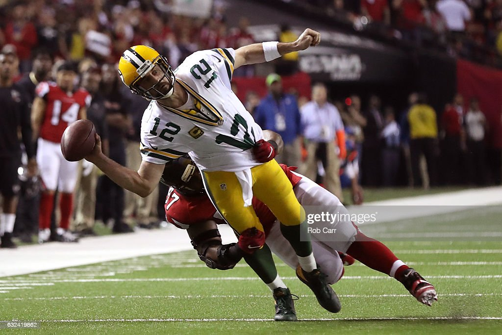Aaron Rodgers #12 of the Green Bay Packers attempts a pass as he is tackled by Grady Jarrett #97 of the Atlanta Falcons in the fourth quarter in the NFC Championship Game at the Georgia Dome on January 22, 2017 in Atlanta, Georgia.
