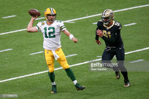 Aaron Rodgers of the Green Bay Packers attempts a pass under pressure from Trey Hendrickson of the New Orleans Saints during the second half at...