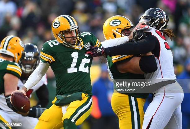 Aaron Rodgers of the Green Bay Packers attempts to get away from Takkarist McKinley of the Atlanta Falcons during the first half of a game at Lambeau...