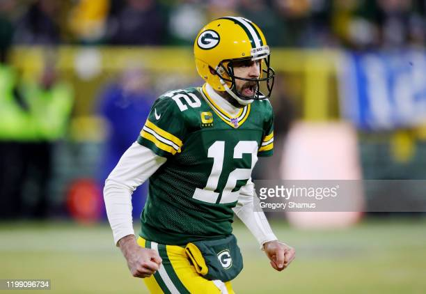 Aaron Rodgers of the Green Bay Packers celebrates after throwing a touchdown pass during the first quarter against the Seattle Seahawks in the NFC...