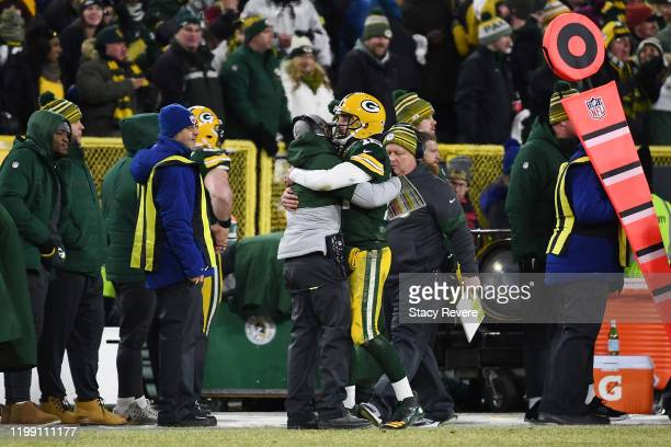 Aaron Rodgers of the Green Bay Packers celebrates with head coach Matt LaFleur on the sideline after scoring a touchdown during the second half...