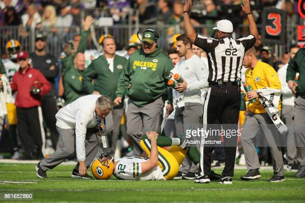 Aaron Rodgers of the Green Bay Packers clenches his right knee after being hit during the first quarter of the game against the Minnesota Vikings on...