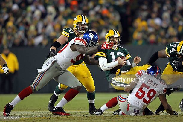 Aaron Rodgers of the Green Bay Packers gets sacked by Jason PierrePaul and Michael Boley of the New York Giants during their NFC Divisional playoff...
