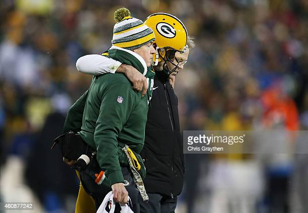 Aaron Rodgers of the Green Bay Packers is helped off of the field after being injured in the second quarter against the Detroit Lions at Lambeau...