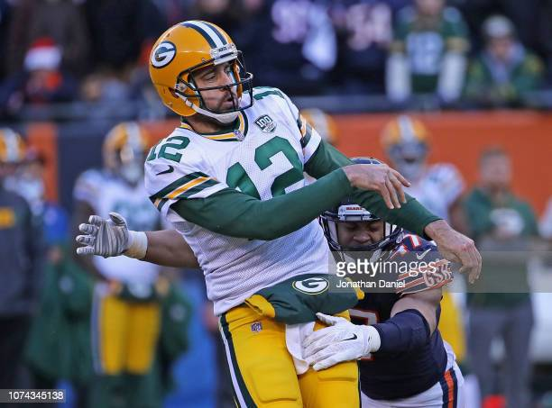 Aaron Rodgers of the Green Bay Packers is hit after passing by Isaiah Irving of the Chicago Bears closes in at Soldier Field on December 16 2018 in...