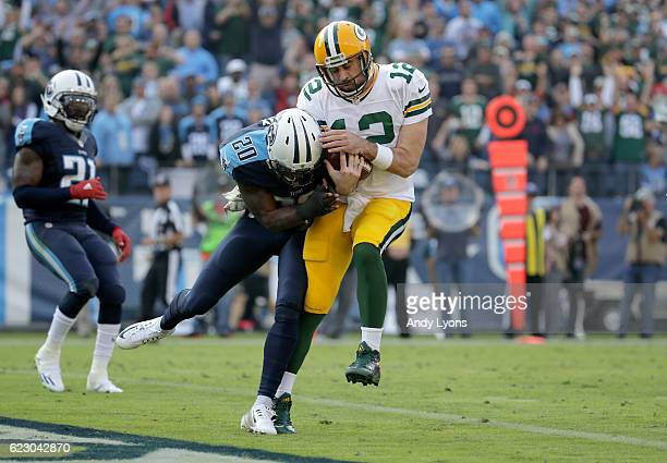 Aaron Rodgers of the Green Bay Packers is hit by Perrish Cox of the Tennessee Titans after he scores a touchdown during the game at Nissan Stadium on...