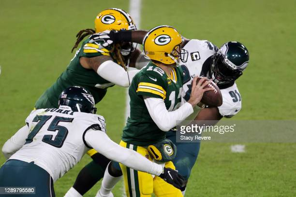 Aaron Rodgers of the Green Bay Packers is pressured by Fletcher Cox and Vinny Curry of the Philadelphia Eagles during the fourth quarter of their...