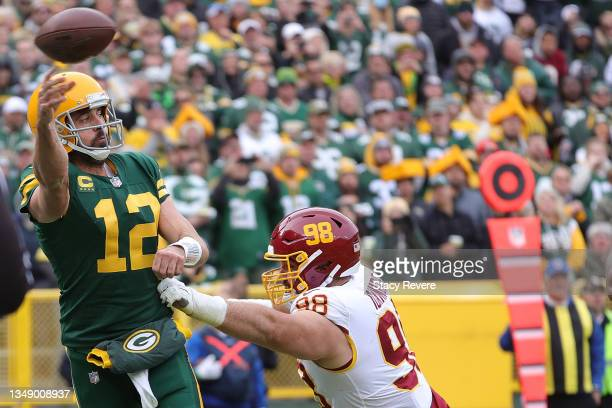 Aaron Rodgers of the Green Bay Packers is pressured by Matthew Ioannidis of the Washington Football Team during a game at Lambeau Field on October...