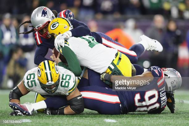 Aaron Rodgers of the Green Bay Packers is sacked by Adrian Clayborn and Trey Flowers of the New England Patriots during the second half at Gillette...