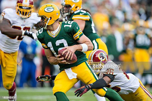Aaron Rodgers of the Green Bay Packers is sacked by Josh Wilson of the Washington Redskins at Lambeau Field on September 15 2013 in Green Bay...