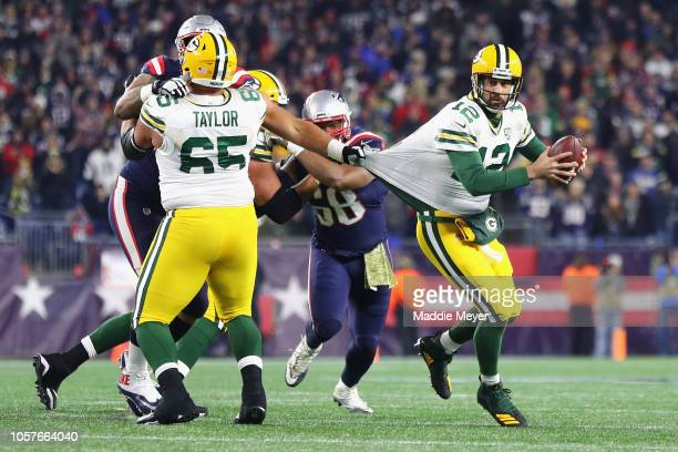 Aaron Rodgers of the Green Bay Packers looks to pass the ball as his jersey is grabbed by Lawrence Guy of the New England Patriots during the second...