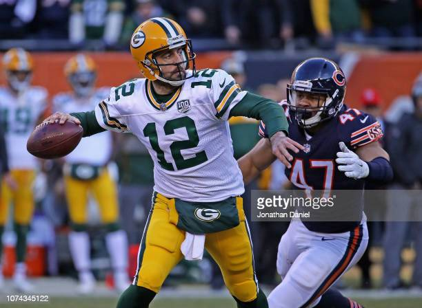 Aaron Rodgers of the Green Bay Packers passes as Isaiah Irving of the Chicago Bears closes in at Soldier Field on December 16 2018 in Chicago...