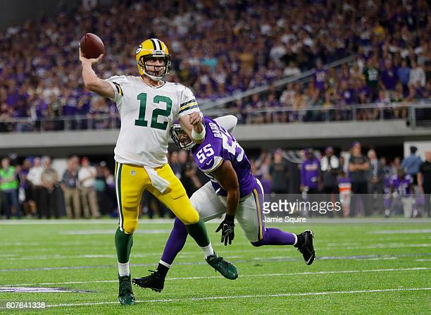 Aaron Rodgers of the Green Bay Packers passes the ball while being pursued by defender Anthony Barr of the Minnesota Vikings during their game on...