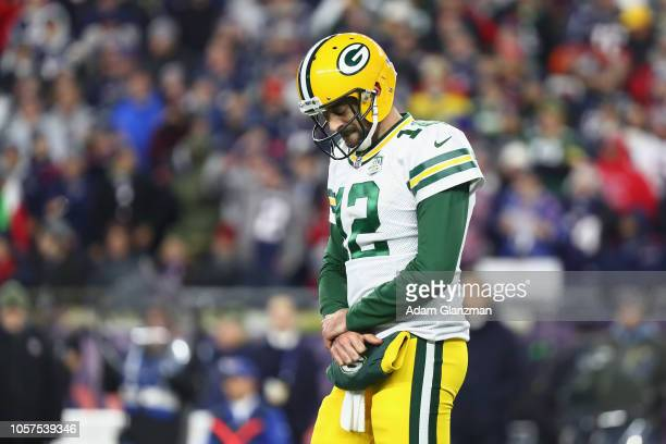 Aaron Rodgers of the Green Bay Packers reacts as he holds his right wrist during the second half against the New England Patriots at Gillette Stadium...