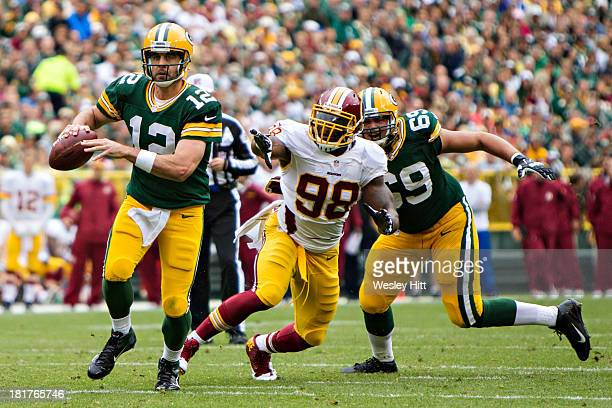 Aaron Rodgers of the Green Bay Packers rolls out looking to pass and is pursued by Brian Orakpo of the Washington Redskins at Lambeau Field on...